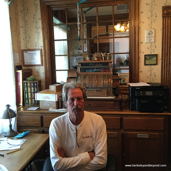 owner Charlie Morgan in front of antique cash register at Jamestown Hotel in Jamestown, California