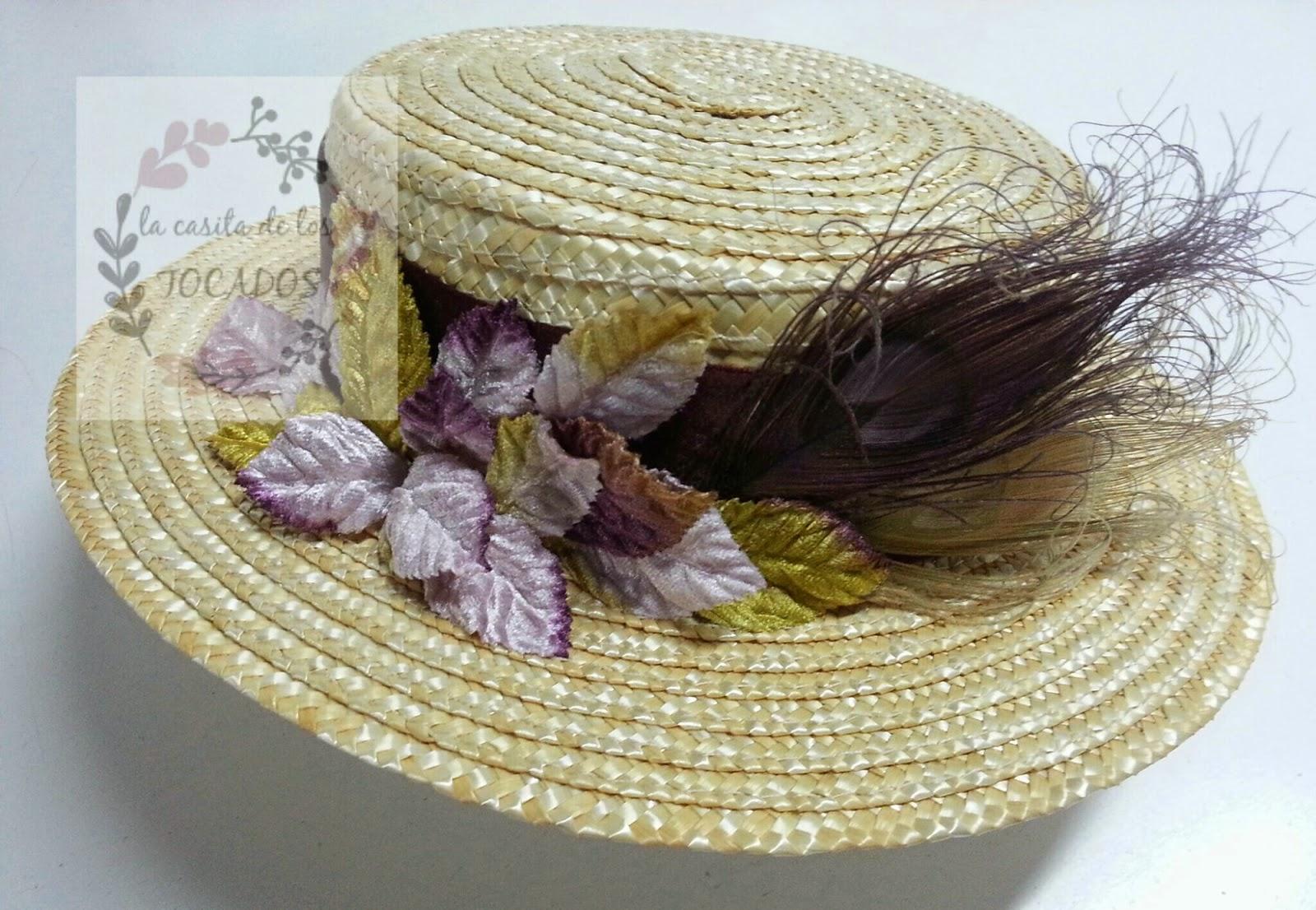 canotier con hojas de terciopelo en dorado, lavanda y vino, además de plumas de pavo real en vino y dorado, y cinta de raso en color vino