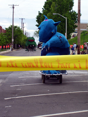 A person in a costume of a creature on large skateboard approaching a finish line.