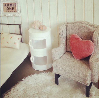 Modern dolls house miniature bedsit scene with a day bed, wing chair, circular fluffy rug and side cupboard in soft shades of white, grey and rose.
