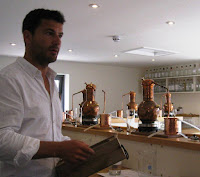 Gin school - one litre copper stills on a shelf above the workbench