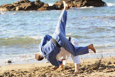 Image of two judo players doing what looks like Ippon Seonage on the beach.What is the Difference Between Summer and Winter in Judo?