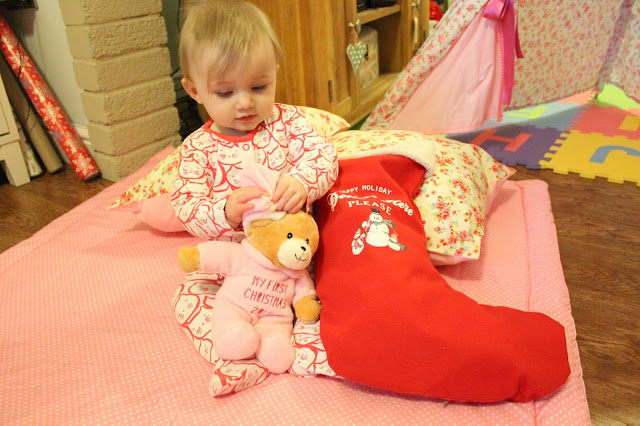 baby's first christmas baby opening stocking with first christmas teddy bear