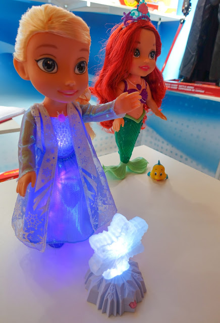 A lit up Elsa doll with arial in the background