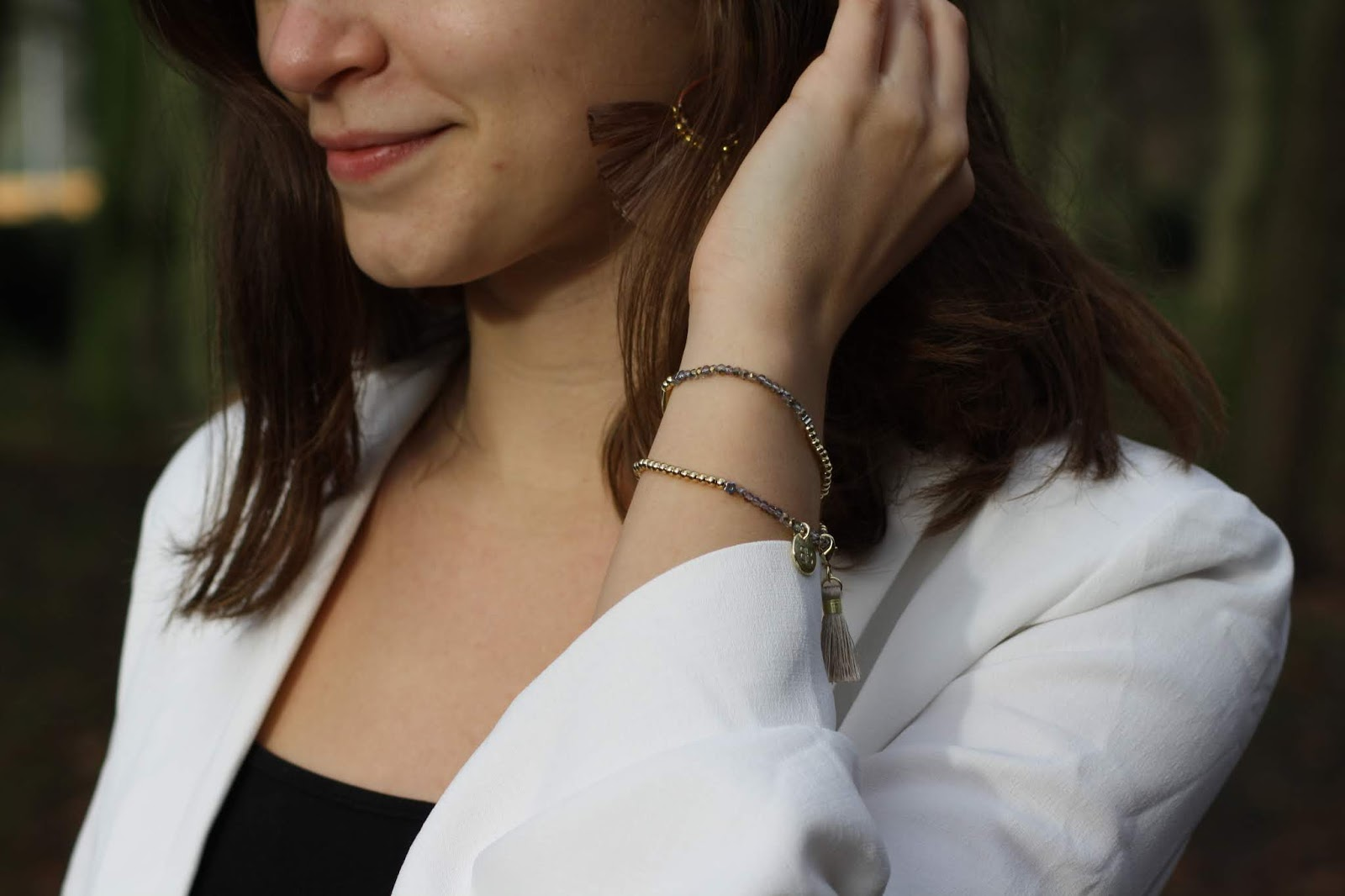 a close up of abbey brushing her hair behind her ear, showing off taupe tassel earrings and tasselled bracelet
