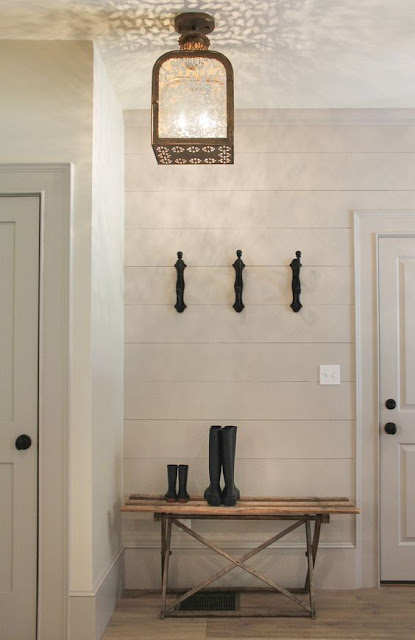Modern farmhouse entry with white ship lap, rustic bench, and boots - found on Hello Lovely