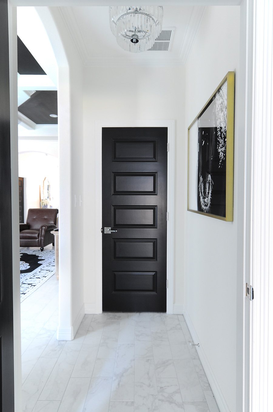 Black interior doors make a bold statement against white walls in this modern home with traditional touches.
