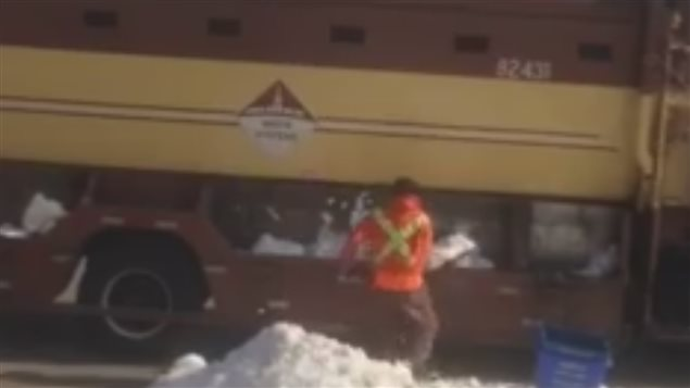 A garbage man filled the snow to garbage truck to get more paid