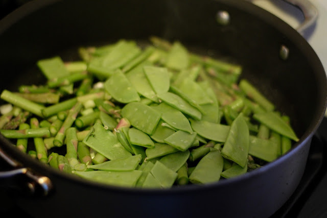 The chopped vegetables in a frying pan on the the stove.