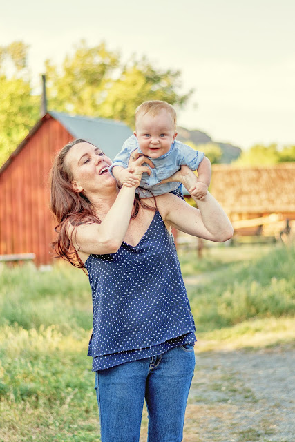 a young mother holds up her adorable baby boy for a candid photo during their portrait session in Golden Colorado