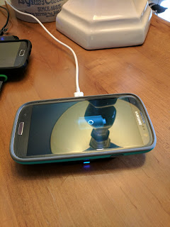 The Samsung Mini Charger Pad wirelessly charging the Galaxy S3.