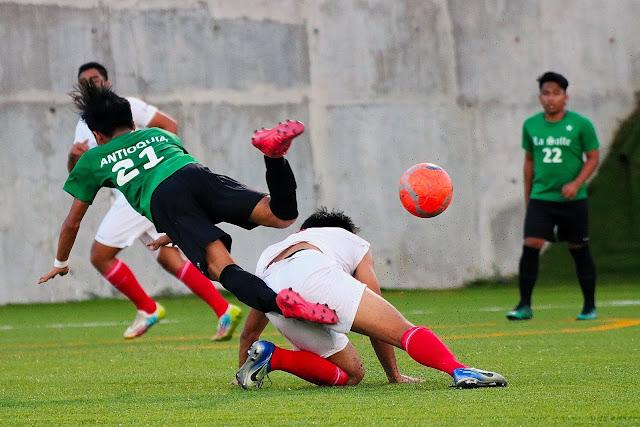 La Salle FC's Gregorio Antioquia trips over Nicolo Pena of ACF Real Molinillo.