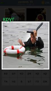 на воде за спасательный круг держится мужчина с ноутбуком на голове