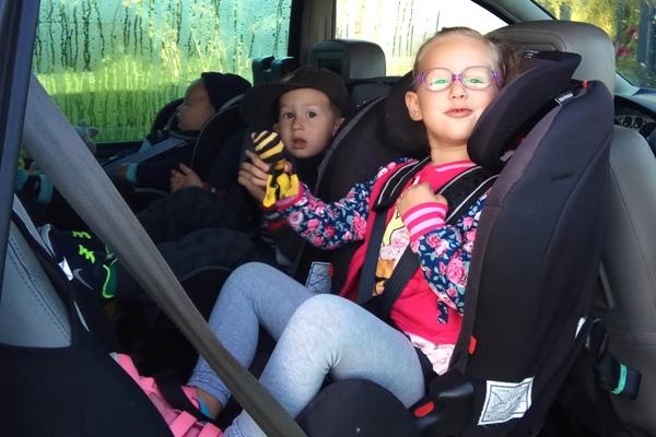trójka dzieci w fotelikach RWF