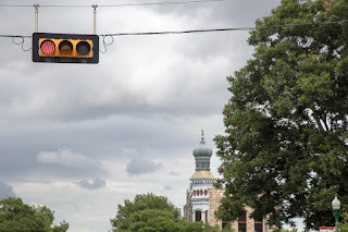 A stoplight on the beautiful Georgetown, Texas square, showcasing an historic onion domed building in the backdrop