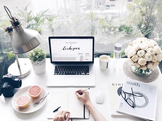 Vintage style blogger desk with laptop, camera, flowers and notebook.