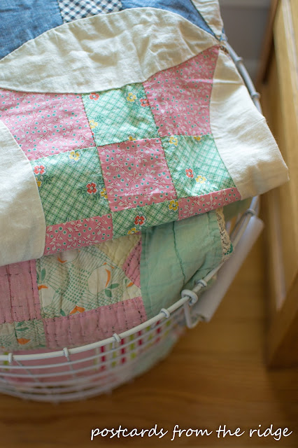 Beautiful old quilts in a basket for decor. Lots of other great ideas on this site. Postcards from the Ridge.