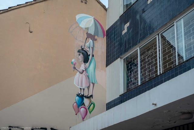 Grafite em uma parede na Rua Inácio Lustosa. Mulher com guarda-chuva, menina com sorvete e balões.