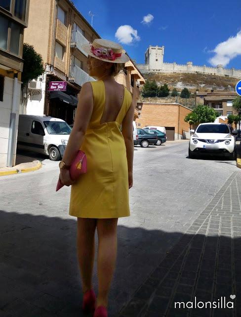 Invitada boda con vestido amarillo corto con escote en la espalda, canotier de flores de copa baja en fucsia y bolso abanico fucsia en la calle con el castillo de peñafiel al fondo