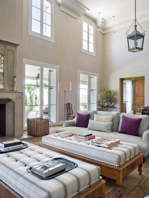living room with high ceiling, fireplace and upholstered sofas