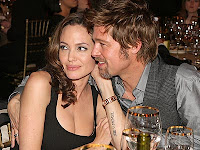 Brad Pitt and Angelina Jolie looking happy and smiling at table