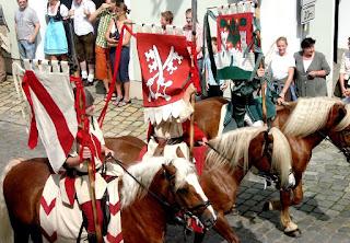 Foto vom historischen Festzug mit drei Standartenreitern