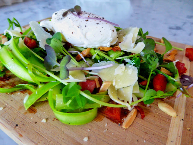 Shaved asparagus salad topped with a poached egg, crisp pancetta, and toasted almonds with a lemon-honey vinaigrette.
