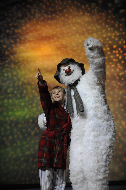 The Snowman and a boy, pointing into the sky and smiling