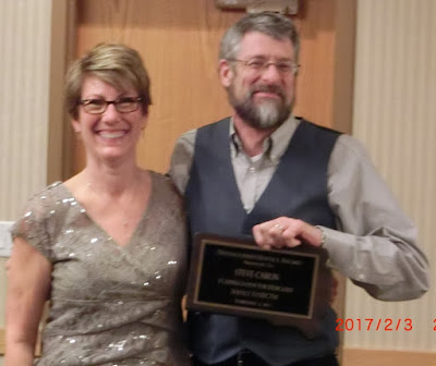 Steve Caron holding award, standing next to Cindy Kroon