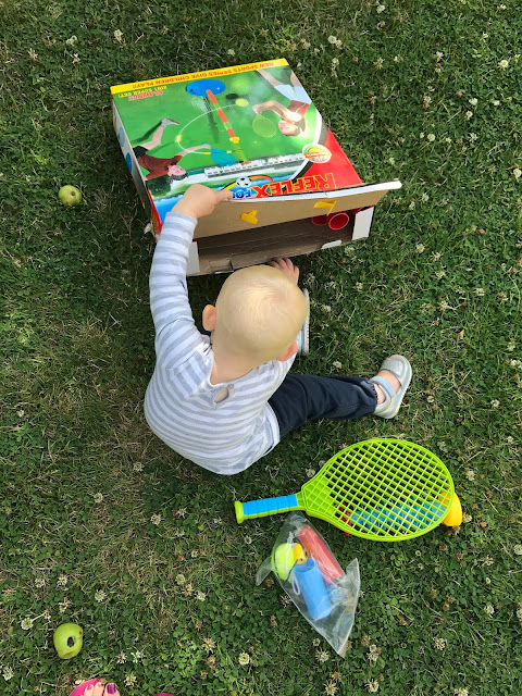 A toddler reaching in to the swing ball box, a plastic racket and other pieces of plastic are already visible on the grass