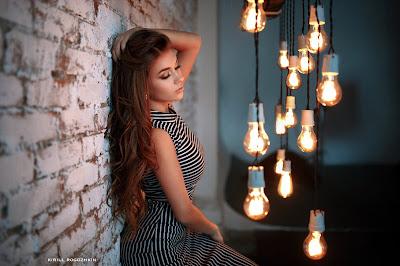 Linda chica apoyada en la pared con luces delante