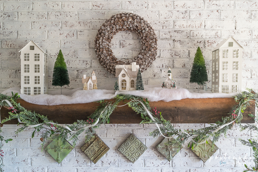 Farmhouse Christmas mantel with house shaped lanterns, pine cone wreath, vintage tin tiles