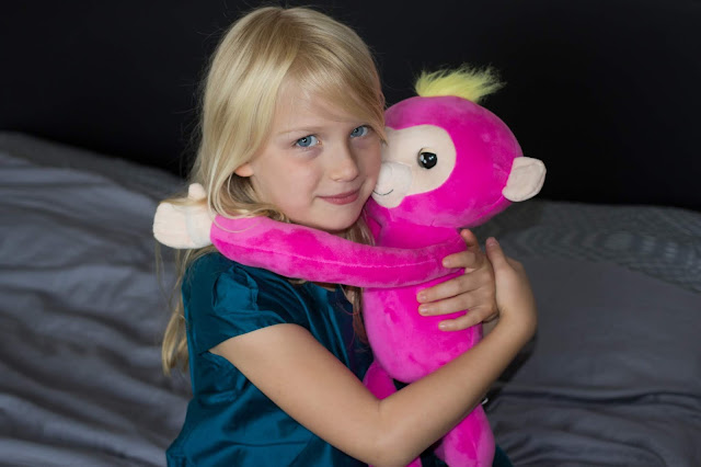 A girl hugging the Fingerlings HUGS