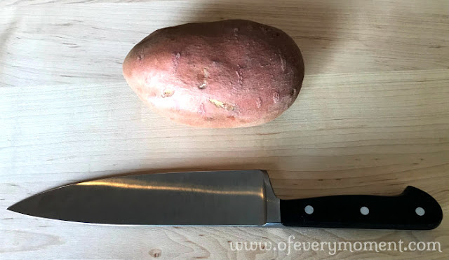 a sweet potato and chef knife on a wooden cutting board