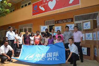 Mrs. Liu Yue, Deputy General Manager of AVIC-INTL Engineering (middle) and employees from AVIC-INTL Engineering with the children from orphanage