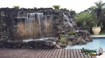 Execução da cascata de pedra na piscina com execução da hidromassagem com um lago de pedra ornamental e a execução do deck de madeira.