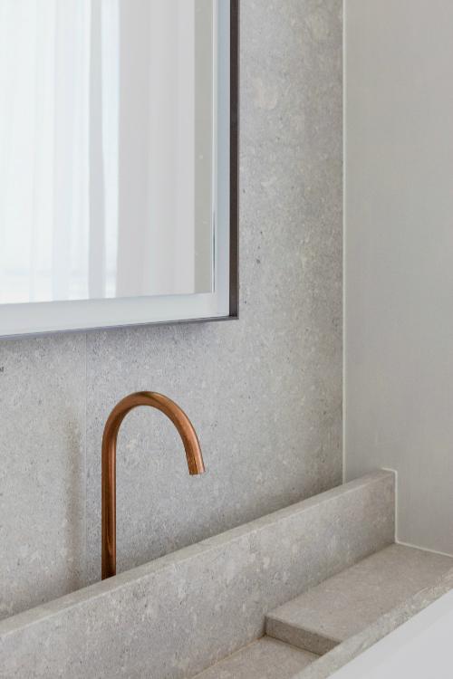 Waschbecken ist aus hellgrauem Stein, die Armatur aus Bronze