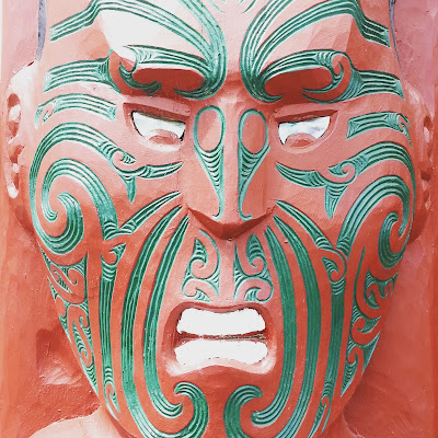 Close up of a maori carving of a face, painted in red and green.