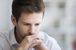 Hombre joven, con camisa blanca, mira al vacío preocupado con la boca apoyada sobre las manos.