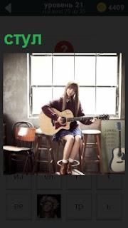 Девушка играет на гитаре, сидя на стуле около окна. Вокруг в помещении еще несколько табуреток