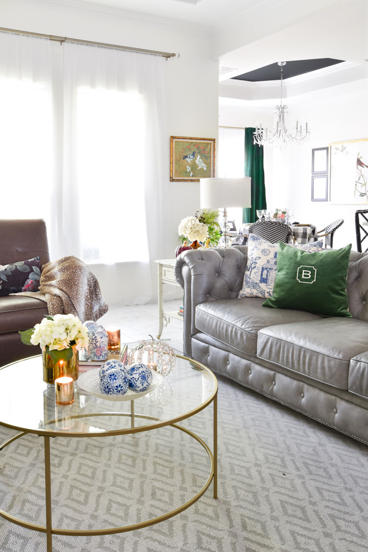 White living room with a gray leather chesterfield sofa paired with chinoiserie accents and emerald velvet drapes.