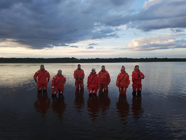 7 pelastautumispukuista ihmistä seisoo polvivedessä.
