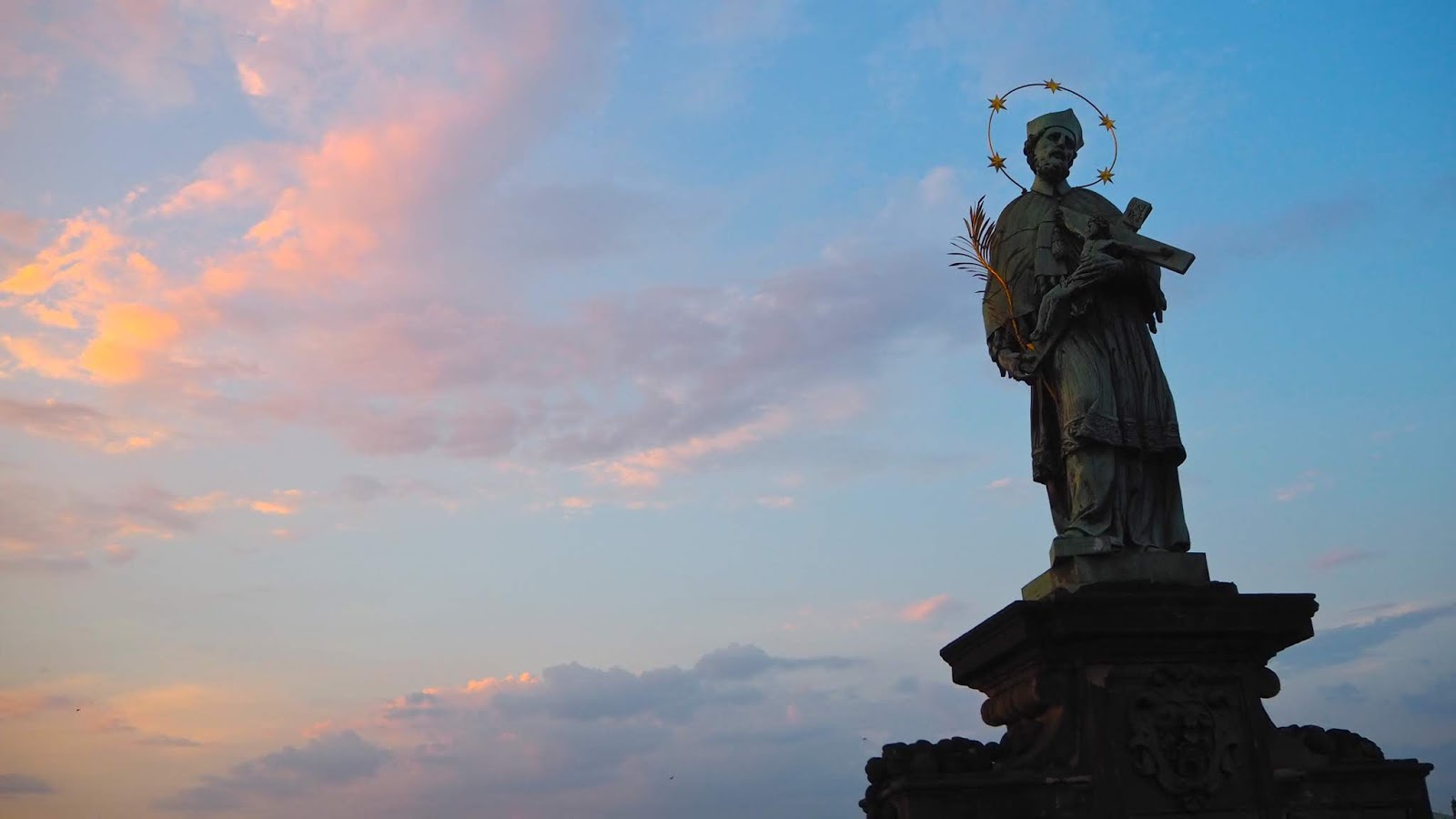 Prague Charles Bridge Statue of a saint at sunset
