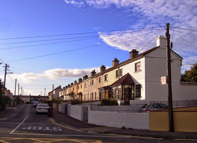 row of city-council built terraced houses in Bohermore, Galway City, Ireland on a sunny day with blue sky.   Houses have parking at the front, and are street-side, there is a compulsory stop painted on the ground at the top of the road and cars parked facing the wrong way in the street