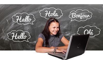 Estudiante de lenguas frente a un computador. Detrás de la chica se observa una pizarra con la palabra hola escrita en distintos idiomas, que son inglés, francés, alemán, español y portugués