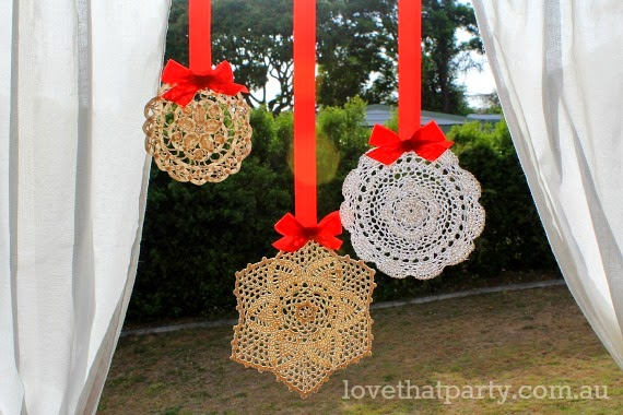 Pretty vintage doilies christmas decoration ornaments hanging from a window