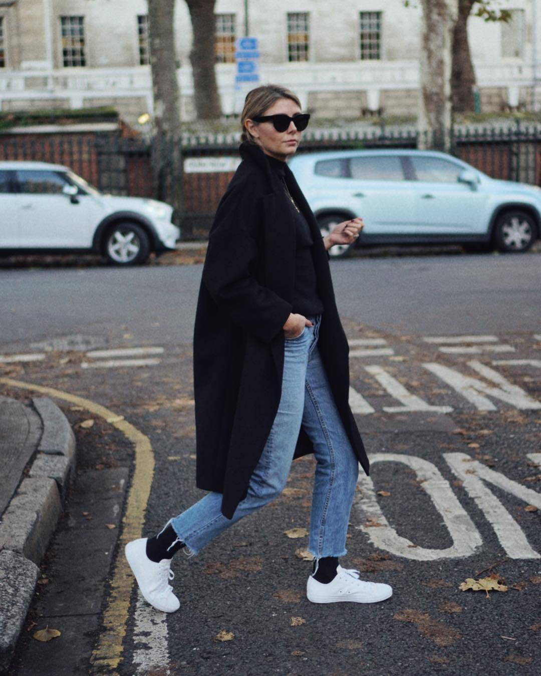 Casual Weekend Outfit for Fall — Black Coat, Raw-Hem Jeans, Black Socks, White Sneakers