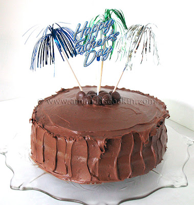 A photo of a nigella\'s chocolate fudge cake with happy father\'s day decorations on top.