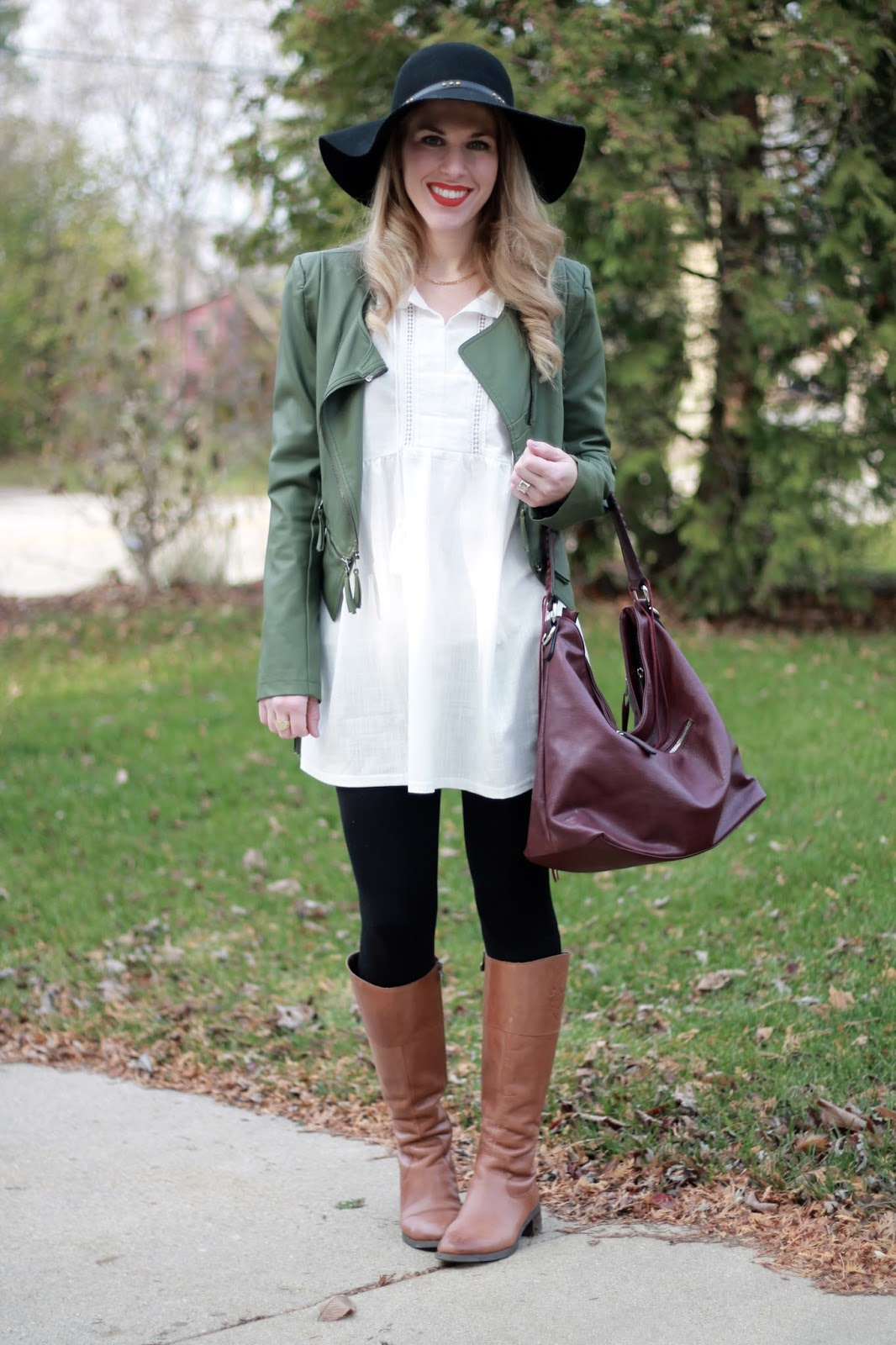 white tunic, black leggings, olive moto jacket, black floppy hat, cognac riding boots, burgundy bag
