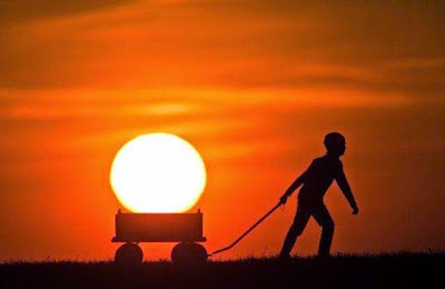 Menino carregando o sol num carrinho de mão